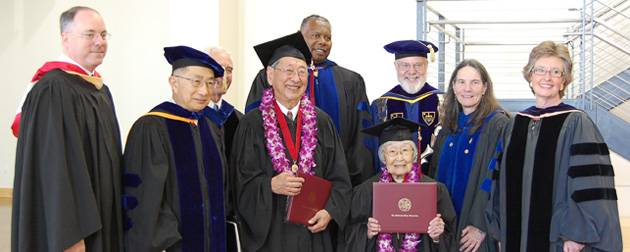 Carl Yoshimine (left, holding degree) and June Junko Kushino (right, holding degree) receiving their degrees in spring 2010.