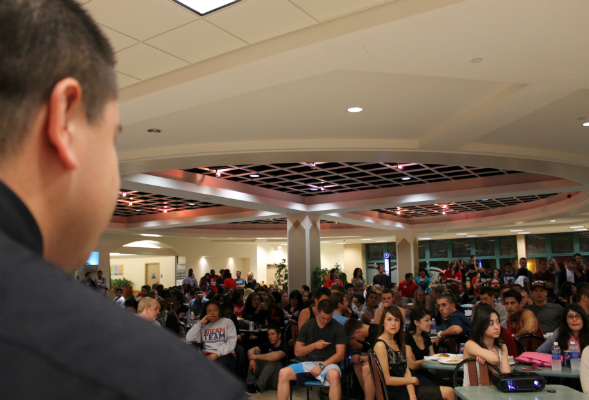 A.S. Elections Committee Chair Omar Espinoza (foreground) speaks to students in East Commons.