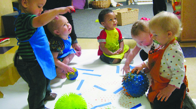 SDSU Children's Center students create art with their teachers and artist-mentor using textured balls and paint.
