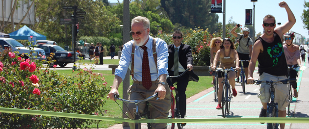 "President Stephen L. Weber (far left) ""cuts"" the ribbon with his bicycle, opening the new campus bike/skate lane."