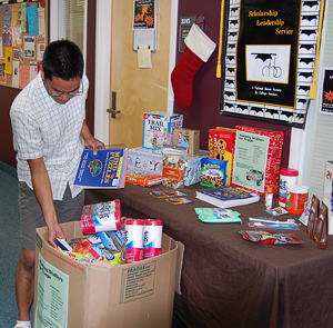 A student provides a donation for Stocking Stuffers for Troops.