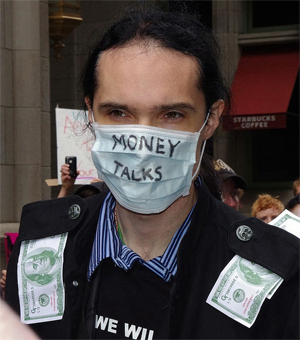 A young man protests corporate greed as part of the Occupy Wall Street movement. Photo by David Shankbone.