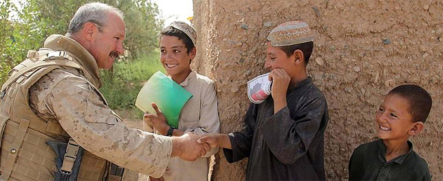 Petty Officer 2nd Class William Lowry, corpsman and Civil Affairs specialist with Regimental Combat Team 3, shakes hands with a local boy during a patrol in Helmand Province, Afghanistan, Aug. 2009.