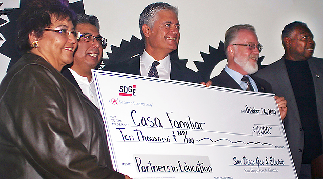 James Kitchen (far right), Stephen Weber (second from right) and Eric Rivera (second from left) accept a check alongside Casa Familiar and SDG&E representatives.