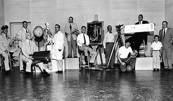 This 1955 photo features San Diego State College's division chairmen. Standing in the middle on the riser is SDSU's first chair of the humanities department, John R. Adams.