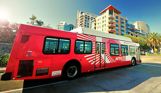 A Metropolitan Transit System bus drives on a city street in San Diego. (Credit: MTS)