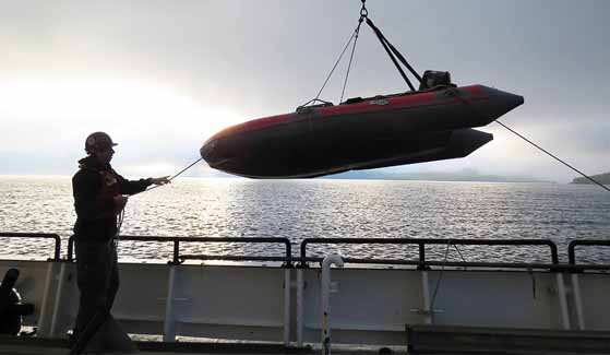 An inflatable dive boat is craned into the water from the R/V Oceanus.
