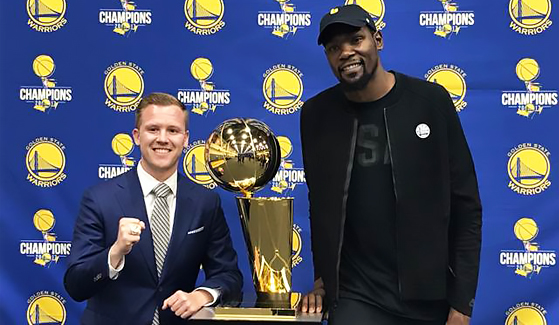 Dominic Lucq (SMBA '14) poses with Kevin Durant and the Larry O'Brien Championship Trophy.