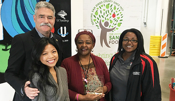 Benita Mann (center) holds the Community Partner Award from the Jacobs & Cushman San Diego Food Bank.