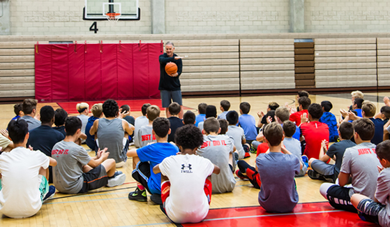 SDSU men's basketball head coach Brian Dutcher speaks to kids at basketball camp.