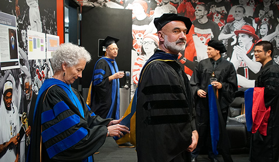 Biology Professor Annalisa Berta provides finishing touches to colleague Roland Wolkowicz's regalia. Photo: Jason Ritchie.