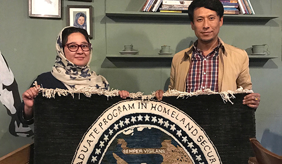 Faheem Eissar (left) in Afghanistan with the rug she wove to hor the education Eesa Ahmadi (right) received from SDSU.