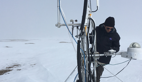 Ecosystem ecologist and post-doctoral fellow Kyle Arndt checking on the measurement equipment set up by SDSU in Utqiagvik (formerly Barrow), Alaska.