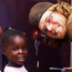 young Peace Corps volunteer alongside smiling little girl