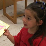 Hadarya, 4, grabs a book to read in Children's Literature Collection.