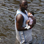 A man carries a baby following the evacuation of the Superdome following Hurricane Katrina in New Orleans. Photo by the U.S. Navy