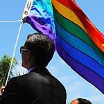 U.S. flag, California flag and the rainbow flag flying at San Diego State University