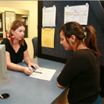 A clerk helping a student in the Office of Financial Aid and Scholarships