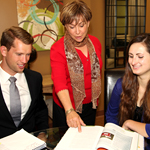 Linda Guzzo, center, checks with Adam Seperack and Lucy Velasquez on the progress of their internships.