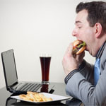 Guy eating a hamburger in front of the computer