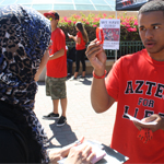 Alumni engagement officer Grayson Coney hands out a bracelet to a fellow SDSU student.