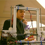 Students examining a 3-D printer