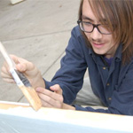 A student painting a bench on campus