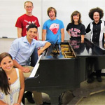 "Members of the ""CURIOSITY"" production pose next to a piano."
