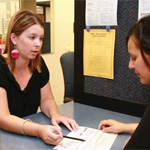A woman at the Financial Aid office helps a student