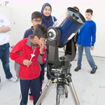 Local elementary school students enjoy roof-top telescope viewing at the Science & Engineering Sampler.