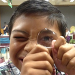 A kid looking through a magnifier