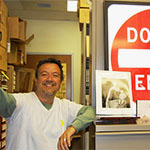 "Professor William Nericcio stands proudly next to his ""Do Not Enter"" road sign."