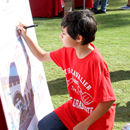 "A student signs the ""I Pledge To Go To College"" board at the Compact for Success 7th Grade Visit to SDSU. (Credit: SDSU Student Affairs Communications Services)"
