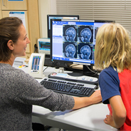 Sarah Reynolds, a research coordinator on Dr. Inna Fishman's team, and a participant reviewed the child's brain images after the scan.