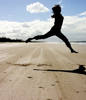 Woman jumping on sand