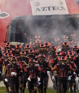 The Football team charges out of the tunnel