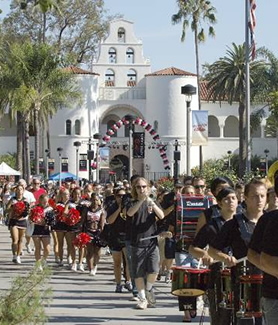 The Marching Aztecs and cheerleaders lead the Band Run through campus.