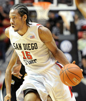Kawhi Leonard dribbles past a defender across the court. (Photo: Ernie Anderson)