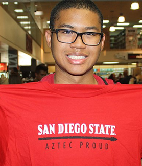 SDSU student Jacob Green holds up the Aztec Proud t-shirt he received after making a donation.
