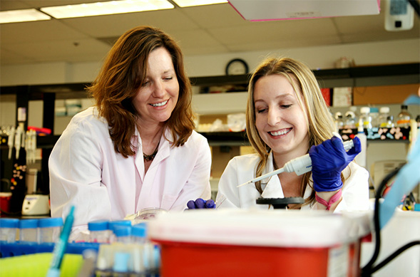 Microbiologist Kelly Doran (left) works with a student.