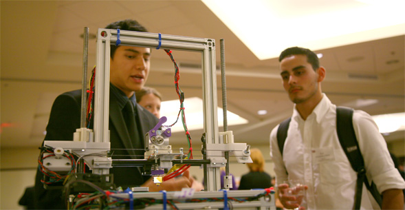 Students examining a 3-D printer.