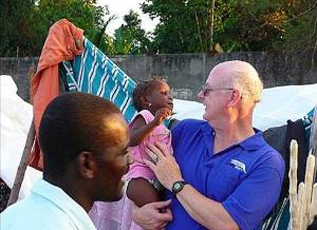 Rich Pickett in Haiti holding young girl