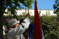 A member of SDSU's Army ROTC gives the flags a final look before the ceremony.