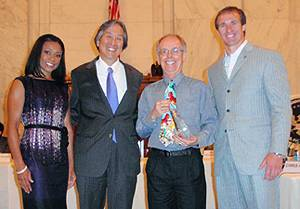 Sallis accepts his award. From left: Dominique Dawes, Howard Koh, Jim Sallis, Drew Brees