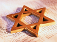 Star of David ornament on an open page of the Torah