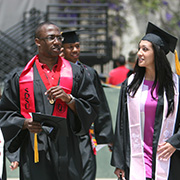 Two students walking in cap and gown