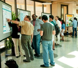 visitors review presentations at the Research Symposium