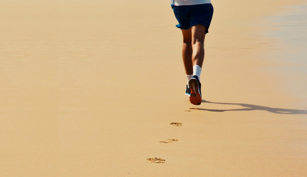 photo of a runner running on the beach