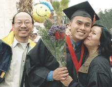 Photo: New graduate posing with parents, with flowers and balloon