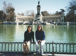 Photo: Two students abroad posing before lake and monument